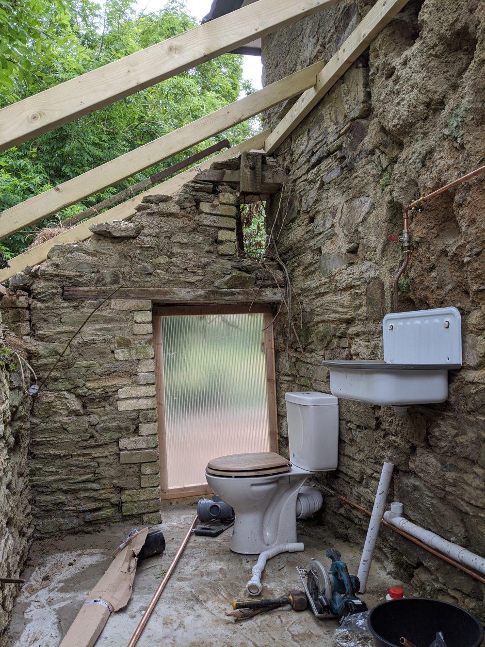 Plumbing in the new toilet, pre roof!